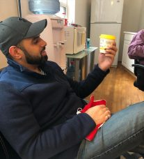 Photo: Hassan, Fonolo's Lead Solutions Engineer, takes a coffee break at the office. He is sitting on a chair, profile to the viewer, looking at his cup of coffee.