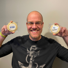 """A photo of Chris smiling and holding up two cookies - one that says """"1M"""" and one that has the Fonolo logo."""