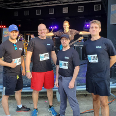 Chris and three of his fellow coworkers stand in front of a stage, ready to participate in a running event