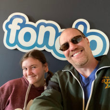 Chris poses in front of the old Fonolo logo with his daughter